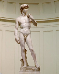 36. Michelangelo Buonarroti, David, 1504, CE, Galleria dell Accademia, Florence, marble. Commissioned by the Cathedral of Florence, David was to be placed in a top niche but was placed on the plaza of Florence's government building instead, representing Florence as a powerful state. It is elongated and disproportional (having longer legs), like Doryphoros's Canon. Unlike Donatello's and Verrocchio's David, its head abruptly turns toward Goliath, showing anticipation. Its colossal, muscular body - typical of Michelangelo - and stern facial expression exert tension and energy. Undercutting created muscles; drilling created curly hair. This unpolished sculpture has archaic smile and facial expression which differs on angle viewed. Many High Renaissance sculptures are Greco-Roman biblical heroes.