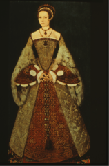 Cone-shaped farthingale, Square neckline and pointed bodice, Hair is hidden under a structured hat. False sleeves with slashing
