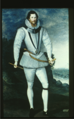 Elizabethan. Elongated body, peascod shaped doublet, short pumpkin breeches over canions. Leg-o-mutton sleeves, ruff and metal gorget around his neck. The garter indicates his membership. Crescents on his shoulders.
