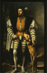 He is wearing upper stocks with a leather jerkin and a coat with black revers. Codpiece. Note the large puffed sleeves, the order and his duck-billed shoes. Flat cap.