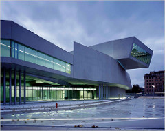 MAXXI National Museum of XXI Century Arts Rome, Italy. Zaha Hadid (architect). 2009 C.E. Glass, steel, and cement. The building is repetitive in that the architecture is supposed to mimic movement to depict the progressiveness of the future of architecture and building.