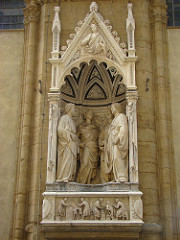 Quattro Santi Coronati by Nanni Di Banco, 15th Cen. Italian Ren - Or San Michele cathedral  - originally meant to be viewed from outside inside  - group of sculptors, masons, etc w/classical attire and serious folding  - controppasto pose, protruding - feet project out, begin to enter viewer's space, integration of human figures in space, monumental size .. saved w/semicircular positioning  - entire section carved into space itself - individuality  - right: open mouth = speaking, other pointing, 2 listening/pondering .. psychological linking of characters  - reduced incised shrunken columns, really miniscule, changing  - humanism and roman form, intensity of saints reverts back to earlier portrayal  - imperial portraiture