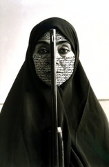 Rebellious Silence, from the Women of Allah series Shirin Neshat (artist); photo by Cynthia Preston. 1994 C.E. Ink on photograph. Photograph, Farsi decorates the artists face, black and white, image shows a veiled woman with the barrel of a gun pointing straight up dividing her face. Her gaze looks directly at the viewer with unwavering confidence.