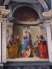 San Zaccaria Altarpiece by Bellini, Venetian  - Madonnas in half-length, large altarpiece - holy conversation, refined compositional elements - virgin w/child in center - st peter w/key and book - st catherine - palm and wheel - st jerome - just book translation bible - angel playing viol in center, placed inside of a shrine, peeks out to outdoor lighting - architecture receeding into architecture, creates apse behind flat wall, frames scene -serenity created with colors, little interaction between figures, lines dissolve, atmospheric haziness, like sfumato - play on depth of space - floor = recession into space