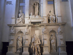 Tomb of Julius II by Michelangelo, High Ren - originally 2 stories w/28 statues, freestanding, ended up smaller and less statues, close off w/volutes  - some meant to be seen from below, but not so impactful  Moses: Leader of Israle, hand grips beard, left leg back as if to stand, give laws, ready to exert energy to throw down laws, awesome power. Deeply undercut, shadow plays, surface patina